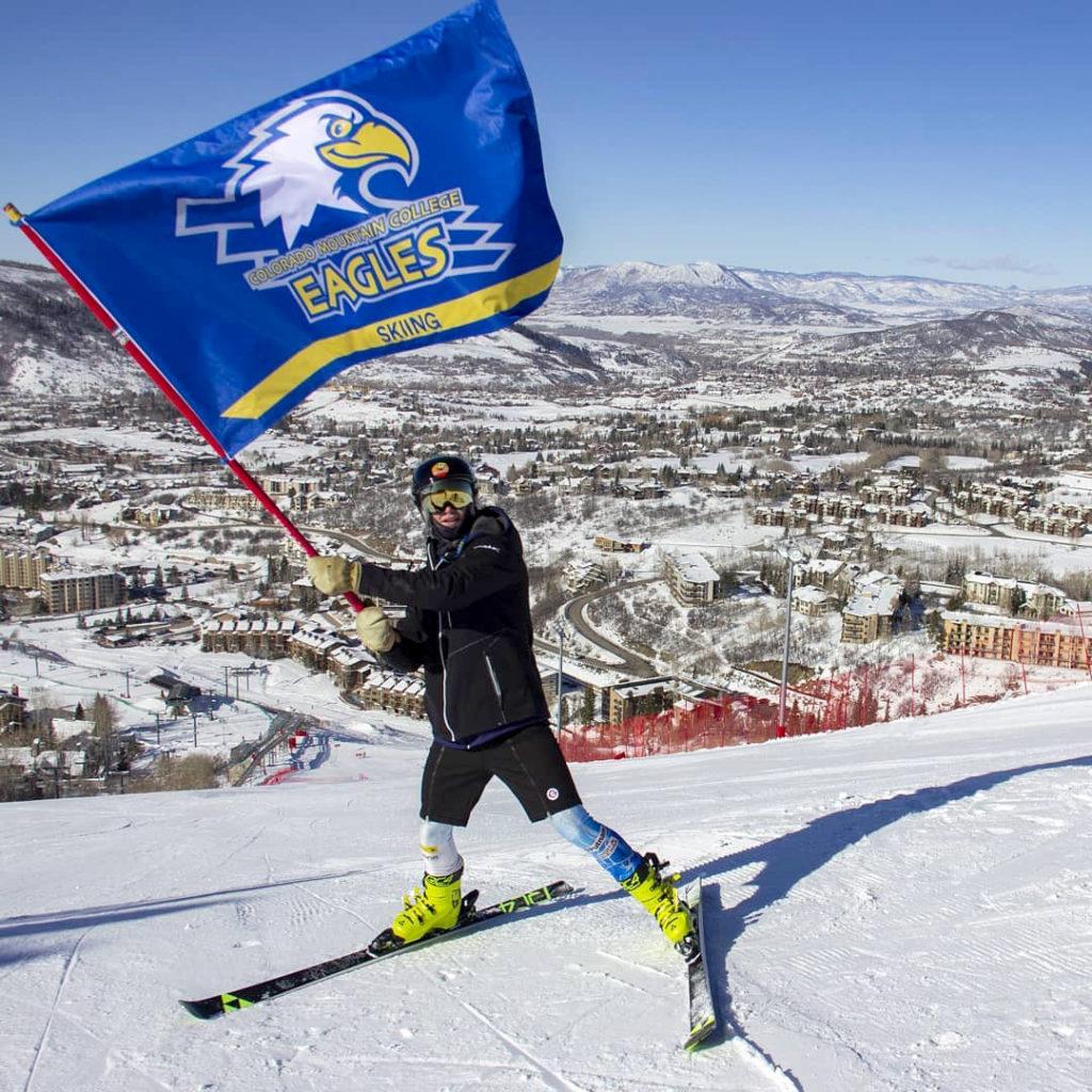 CMC Ski Team member waving team flag.