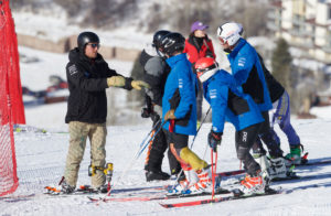 The CMC Ski Team and coach on the mountain discussing a race course.